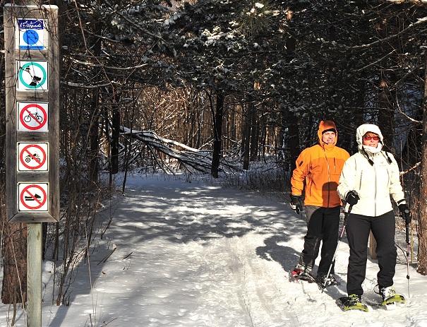 L_Escapade_les_Sentiers_du_Mont_Rigaud-en-hiver-deux-adultes-en-raquette-Signalisation-Photo-courtoisie-Tourisme-Suroit