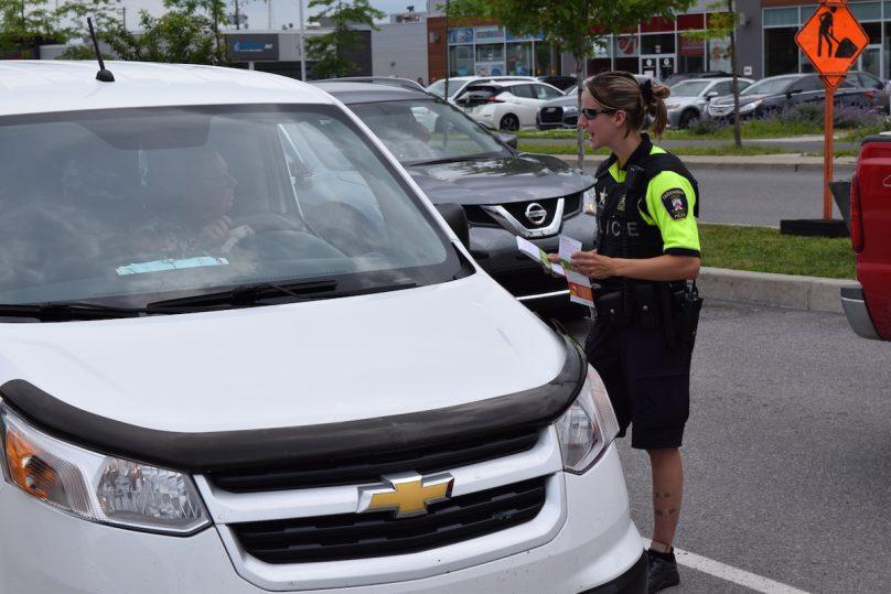 agent police Chateauguay avec automobiliste pour campagne securite Pas de cell au volant photo MRC